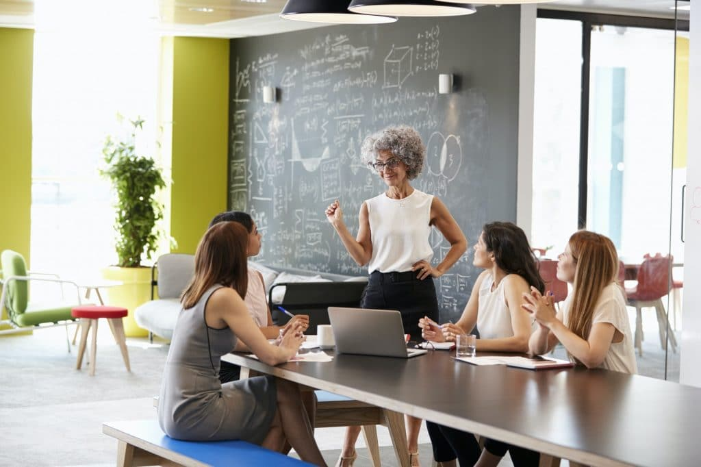 Female boss standing at an informal team meeting